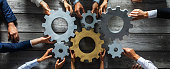 istock Business people joining gears 1254347556