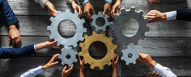 Group of business people joining together silver and golden colored gears on table at workplace top view