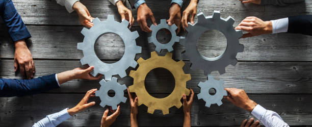 Business people joining gears Group of business people joining together silver and golden colored gears on table at workplace top view collaboration stock pictures, royalty-free photos & images