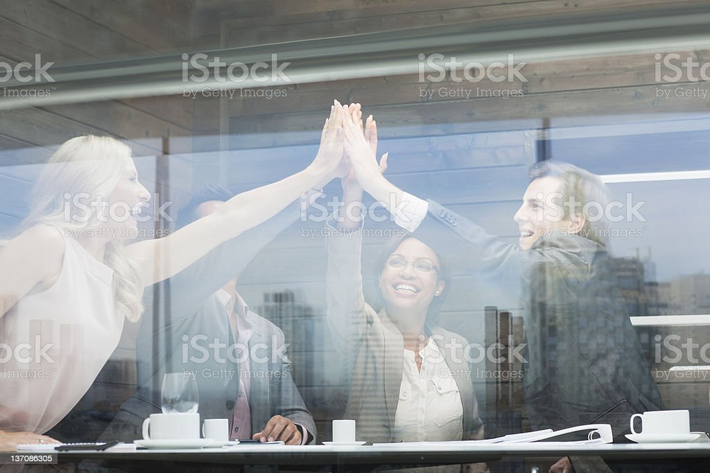 Business people joining hands in conference room stock photo