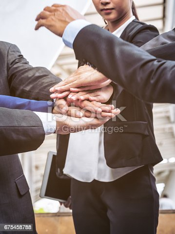 istock Business people joining hands showing teamwork 675458788