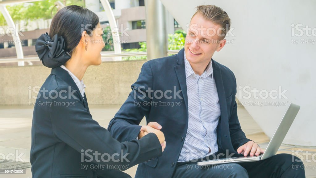business people lady and caucasian smart man with smart phone and cup of coffee and talk presentation on laptop and shake hand royalty-free stock photo