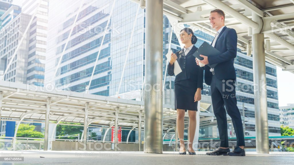 business people lady with hamburger breakfast in hands and caucasian man talk together with feeling happy royalty-free stock photo