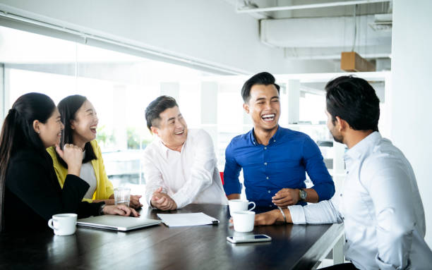Business people laughing in meeting Multi racial business people with laptop on table, sitting together and smiling business Malaysia stock pictures, royalty-free photos & images