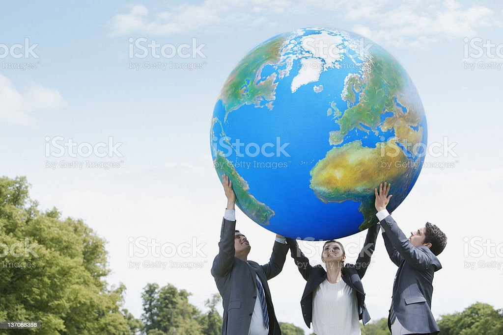 Business people lifting large ball together stock photo