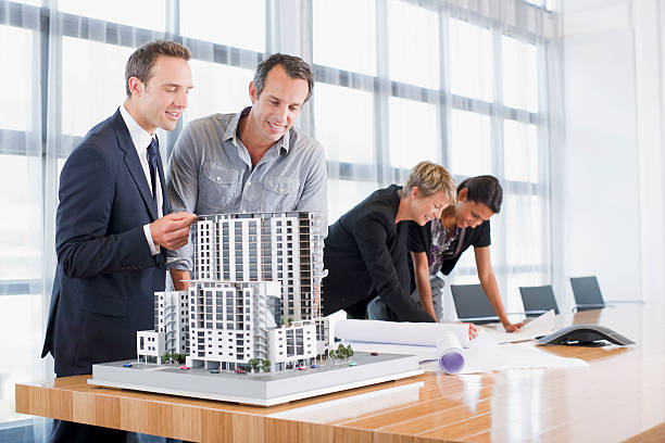 Business people looking at blueprints and model building stock photo