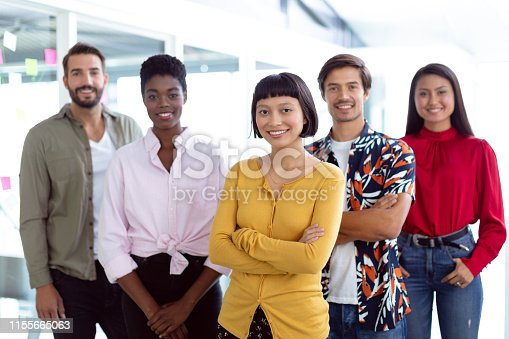 Front view of young diverse business people looking at camera in a modern office