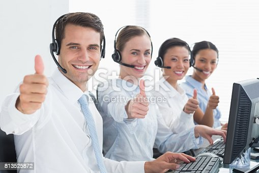 istock Business people looking at camera with thumbs up 813525872