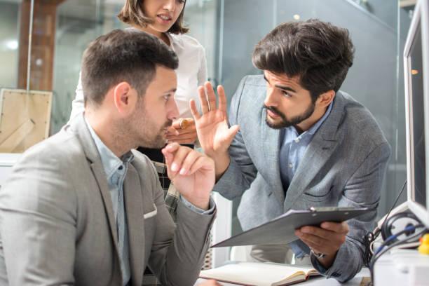Geschäftsleute, die sich gegenseitig anschauen und über Dokumente am Arbeitsplatz streiten – Foto