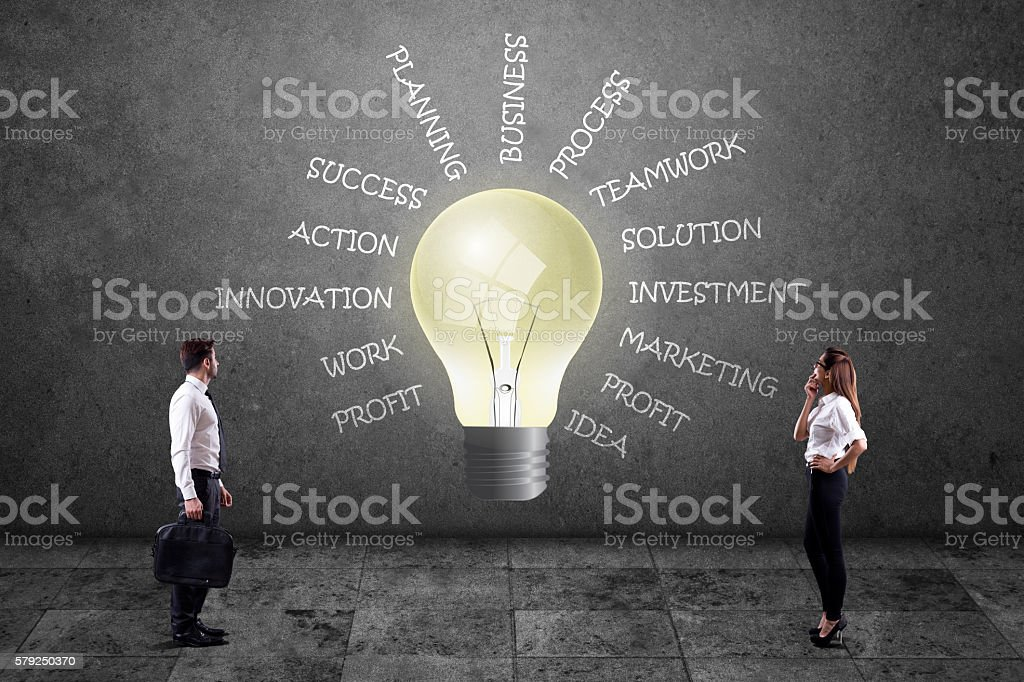 Business people looking at lightbulb with business words stock photo