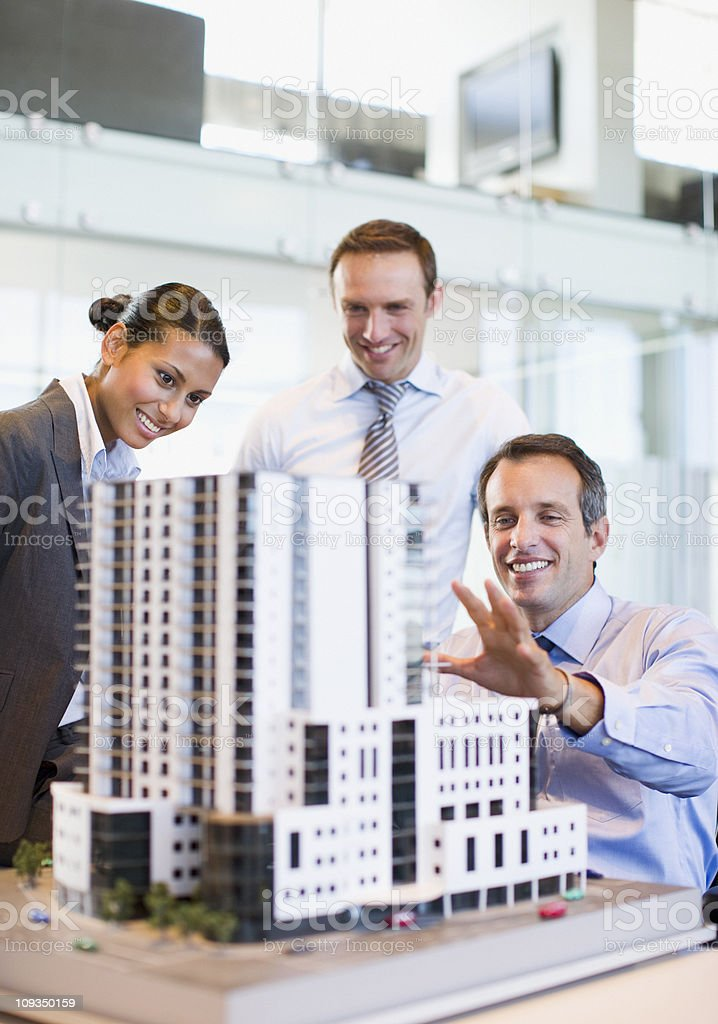 Business people looking at model building in office royalty-free stock photo
