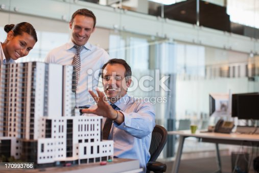 istock Business people looking at model building in office 170993766