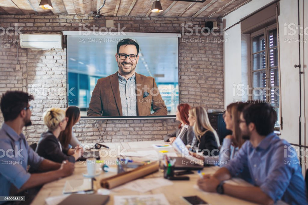 Business people looking at projector during video conference in office stock photo