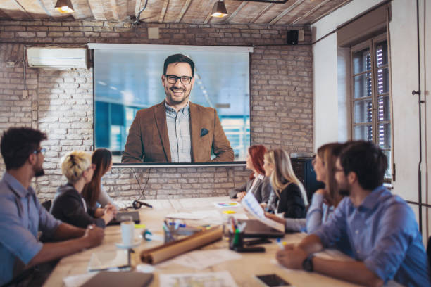 business people looking at projector during video conference in office - projection screen stock photos and pictures