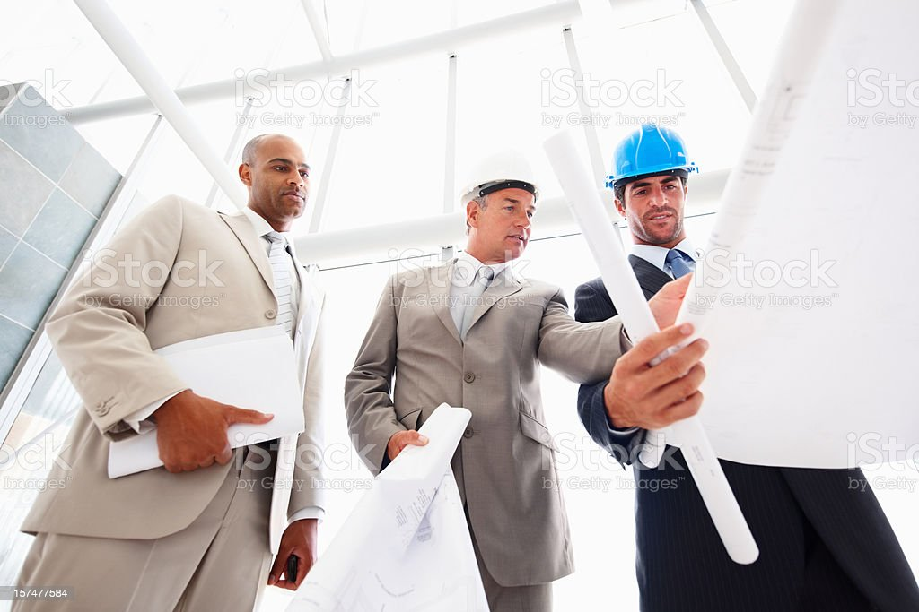 Business people looking at the blueprint royalty-free stock photo