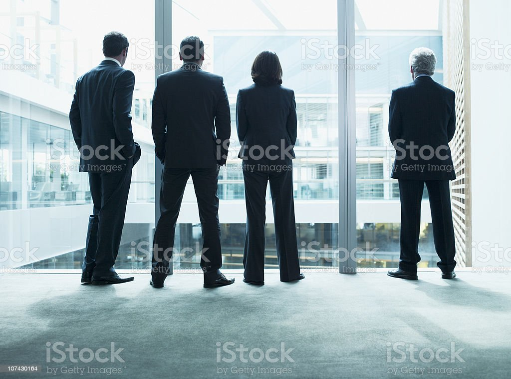 Business people looking out glass wall together stock photo