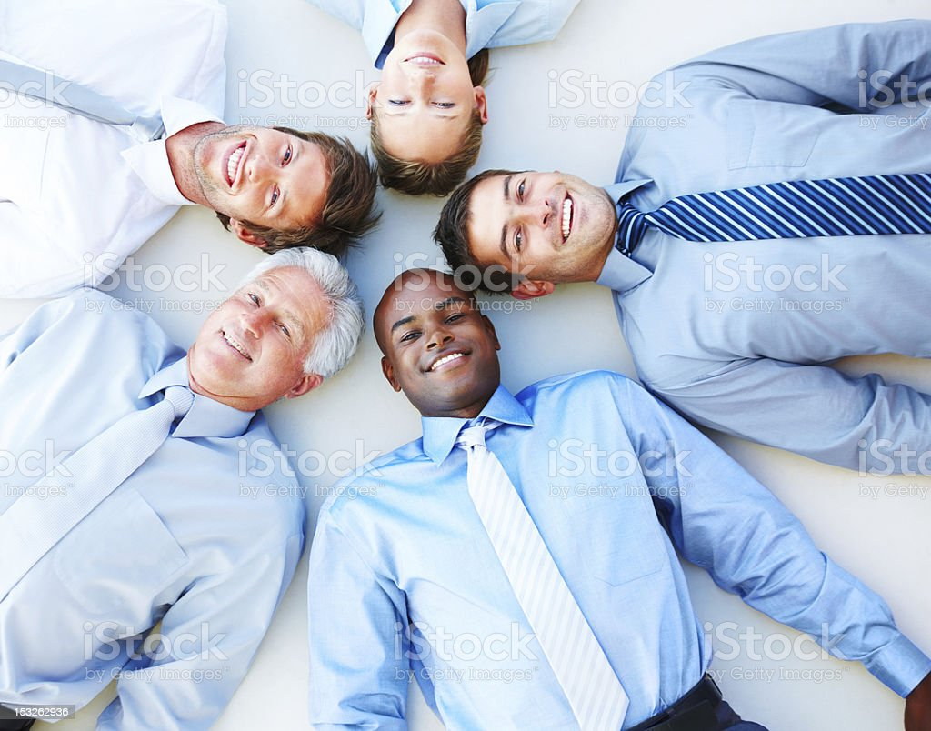 Business people lying down in a circle and looking upwards royalty-free stock photo