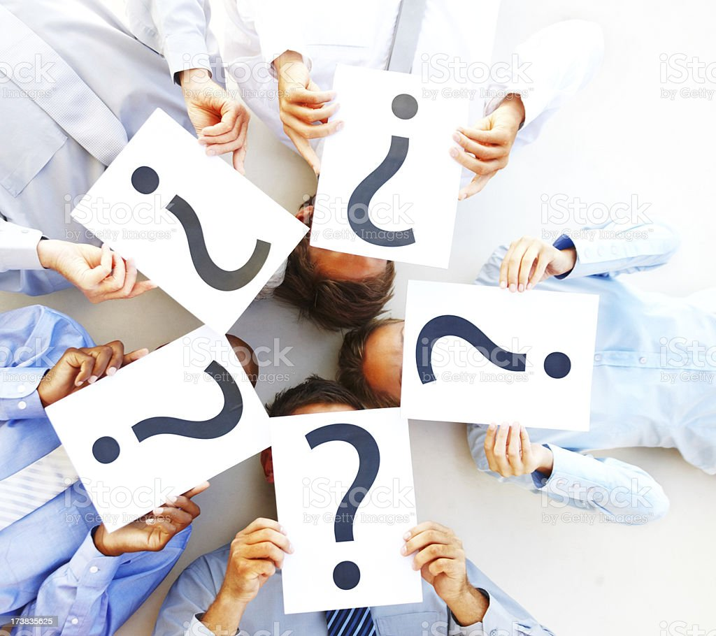 Business people lying on floor holding board with question mark royalty-free stock photo