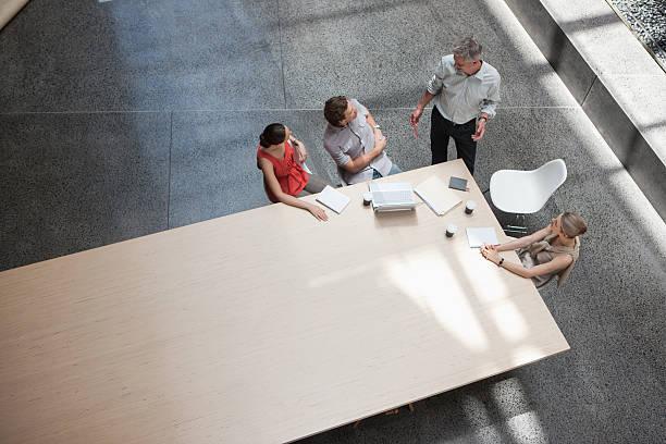 uomini d'affari seduti al tavolo delle conferenze - business meeting, table view from above foto e immagini stock