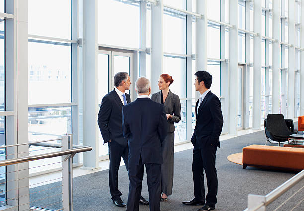 Business people meeting at window in office lobby stock photo