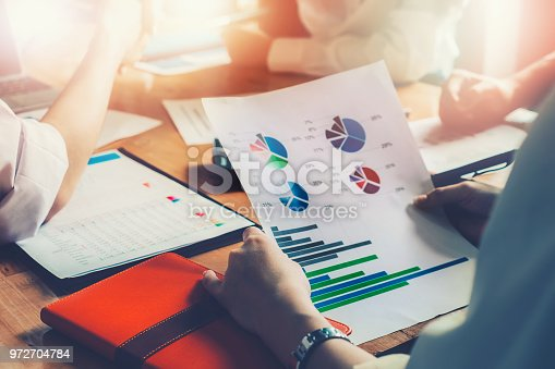 950986656istockphoto Business people meeting at work, with team hand holding stock market chart document to be market research data of company. 972704784