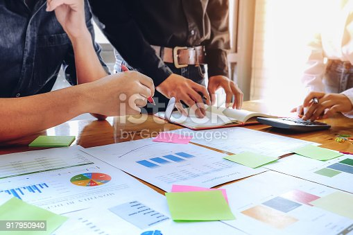 881542122istockphoto Business People Meeting Corporate Communication with using pen, notebook, calculator and stock market chart in at office. Teamwork Concept 917950940