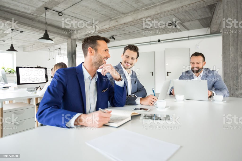 Business people meeting for project discussion Portrait of happy group of business people sitting at a table and working. Three corporate professionals meeting for project discussion in modern office space. Adult Stock Photo