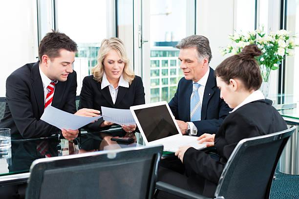 business people - meeting in an office - four lawyers stockfoto's en -beelden