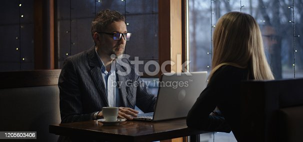 Medium shot of businessman greeting young woman in cafe