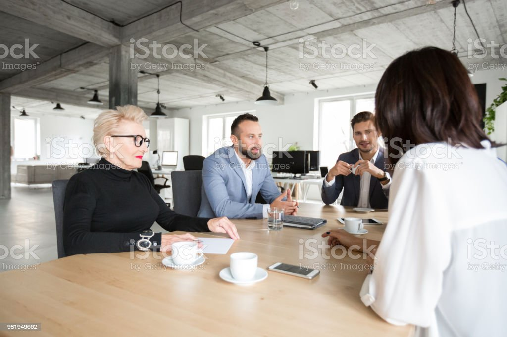 Business people meeting in modern office space Group of corporate professionals sitting around a table and discussing. Business people meeting in modern office space. Active Seniors Stock Photo