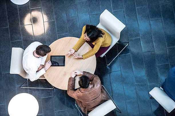 business people meeting in modern office, view from above - three people stock photos and pictures