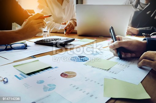 881542122istockphoto business people meeting in office, businessman holding pen and partner use laptop computer on wood desk for Plans to marketing improve quality next year. 914714236