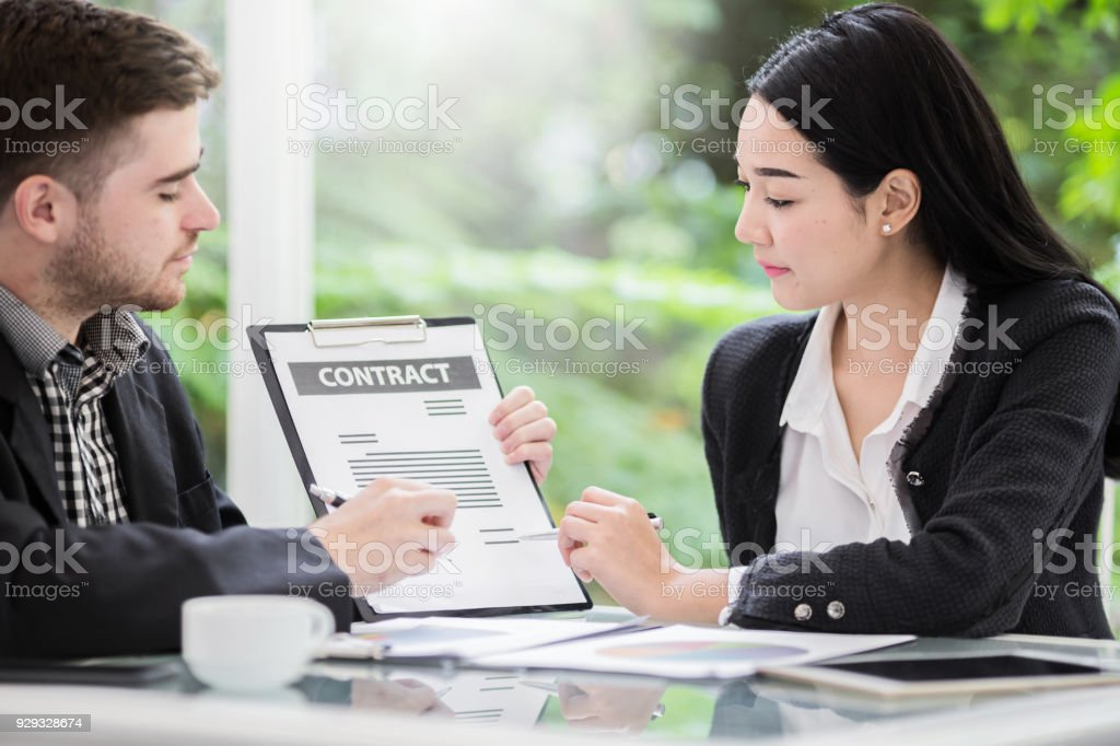 Business people meeting signing agreement sitting at desk team work group on conference discussing financial diagram graph business charts stock photo