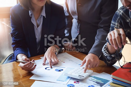 Business People Meeting using calculator,notebook,stock market chart paper for analysis Plans to improve quality next month. Conference Discussion Corporate Concept