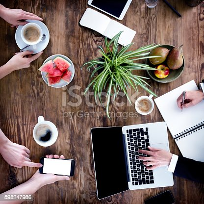 Working Desk – Top View Of Women Hands Using Laptop And Smartphone, Writing In Notebook, Drinking Coffee – Sitting By The Wooden Table Surrounded With Plant And Fresh Fruits