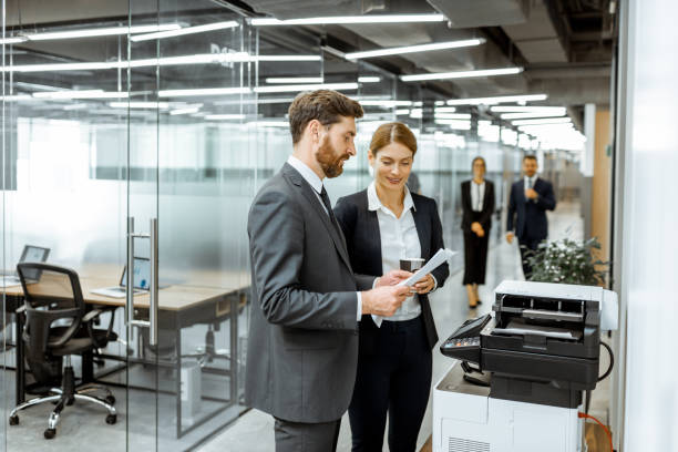 Business people near the copier in the hallway stock photo
