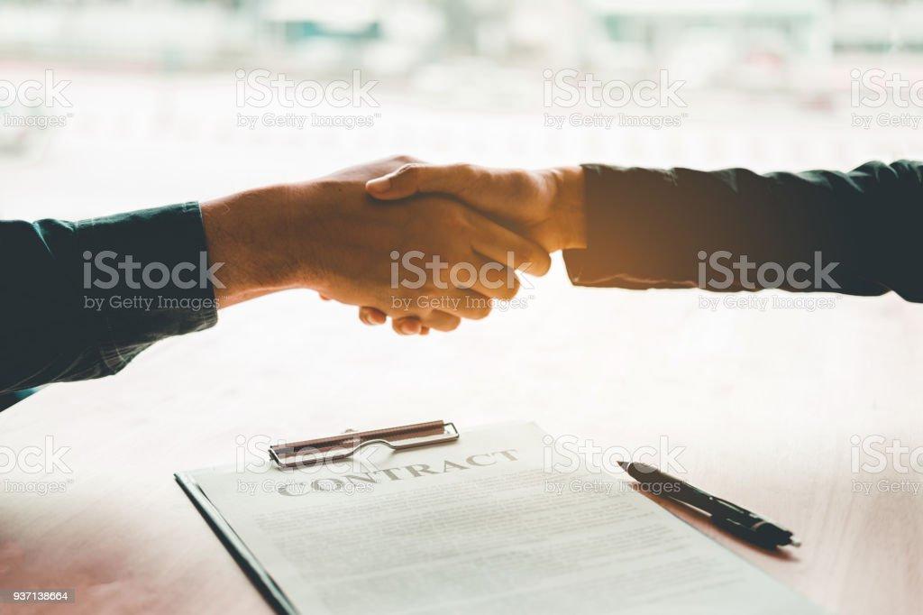 Empresarios negociando un apretón de manos de contrato entre dos colegas foto de stock libre de derechos