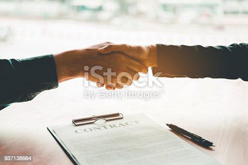 istock Business people negotiating a contract handshake between two colleagues 937138664
