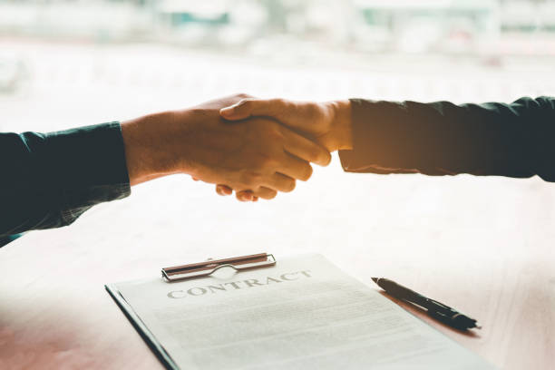 Business people negotiating a contract handshake between two colleagues stock photo