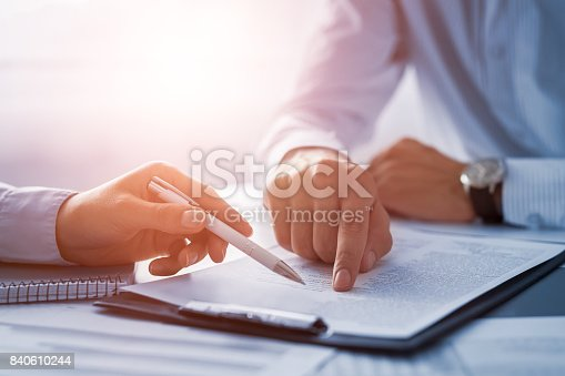 istock Business people negotiating a contract. Human hands working with documents at desk and signing contract. 840610244