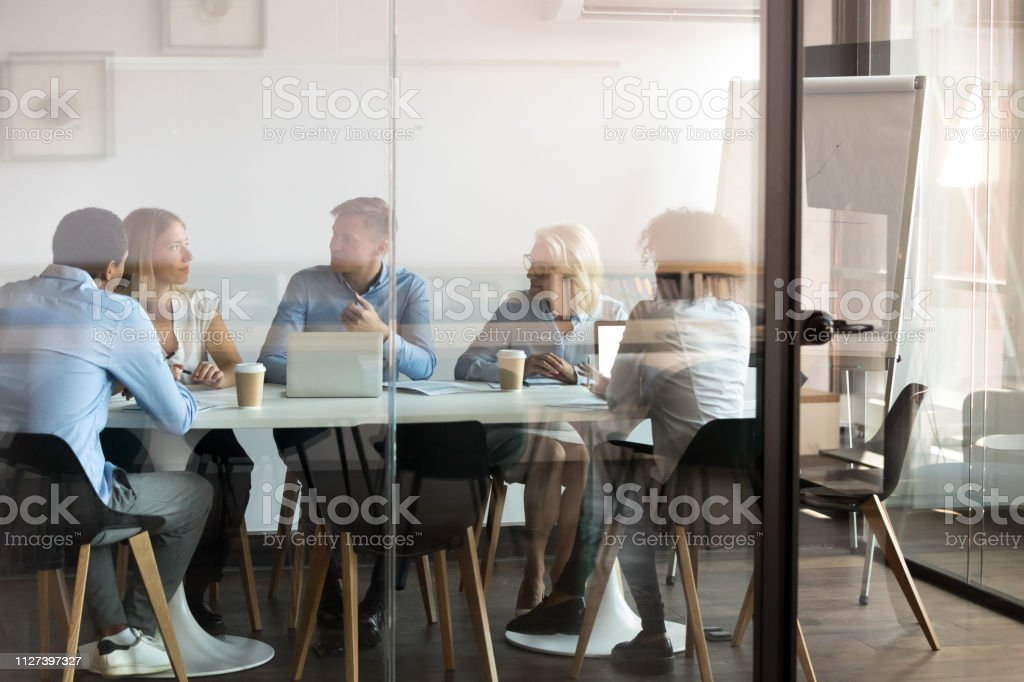 Business people negotiating at boardroom behind closed doors Advertising department brainstorming at modern office boardroom behind closed doors, view through the glass wall. Diverse staff led by ceo discussing new project sharing ideas thoughts and sales pitch Adult Stock Photo