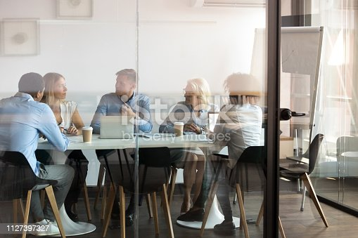 Advertising department brainstorming at modern office boardroom behind closed doors, view through the glass wall. Diverse staff led by ceo discussing new project sharing ideas thoughts and sales pitch