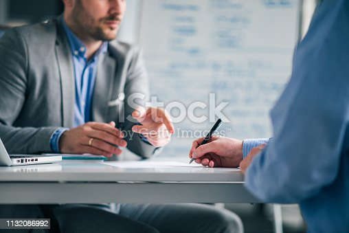 Business people negotiating, signing a contract, close-up.