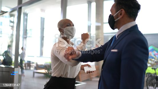 istock Business people on a safety greeting for covid-19 on office's lobby - with face mask 1264813147