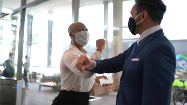 Business people on a safety greeting for covid-19 on office's lobby - with face mask Business people on a safety greeting for covid-19 on office's lobby - with face mask arrival stock pictures, royalty-free photos & images