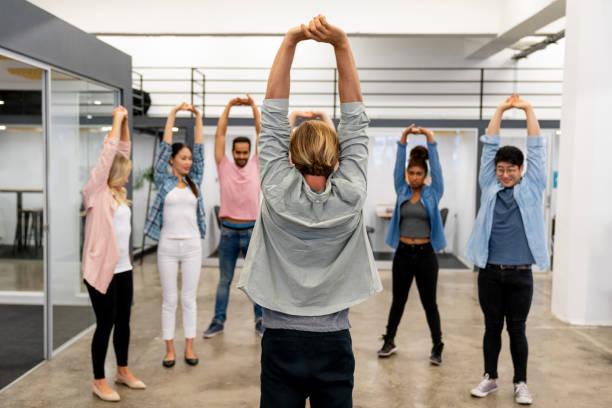 geschäftsleute auf eine aktive pause bei einem kreativ-büro - yoga fürs büro stock-fotos und bilder
