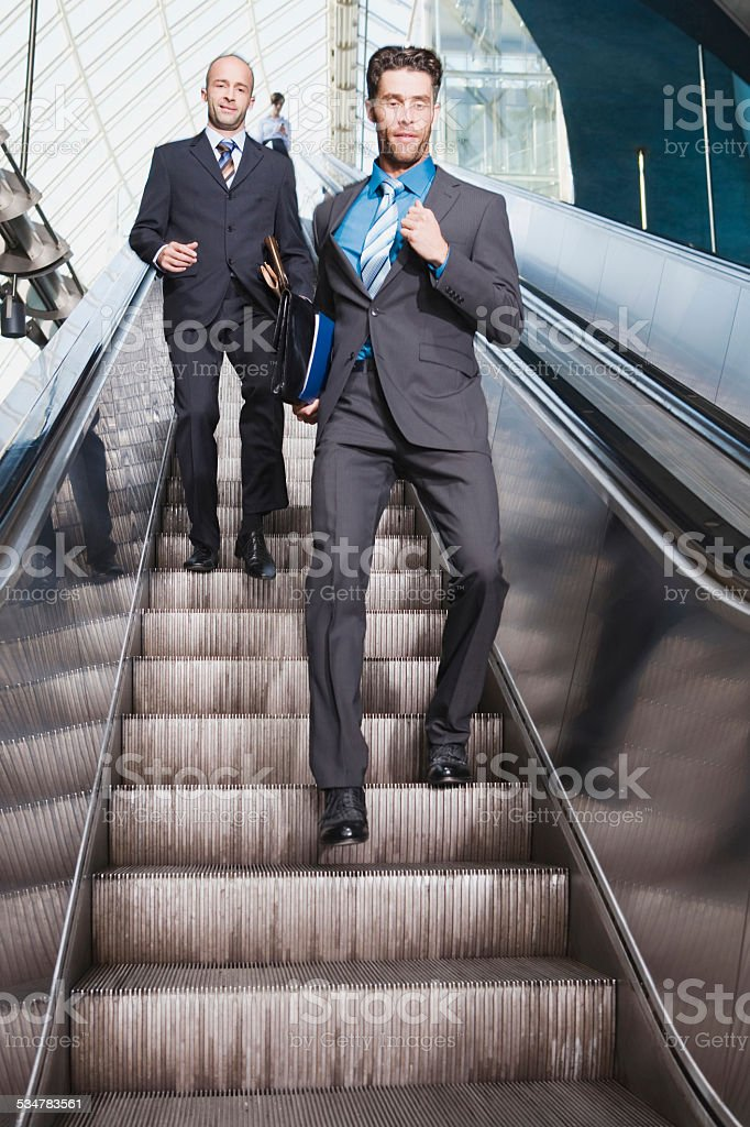 Business people on escalator business man running downstairs stock photo