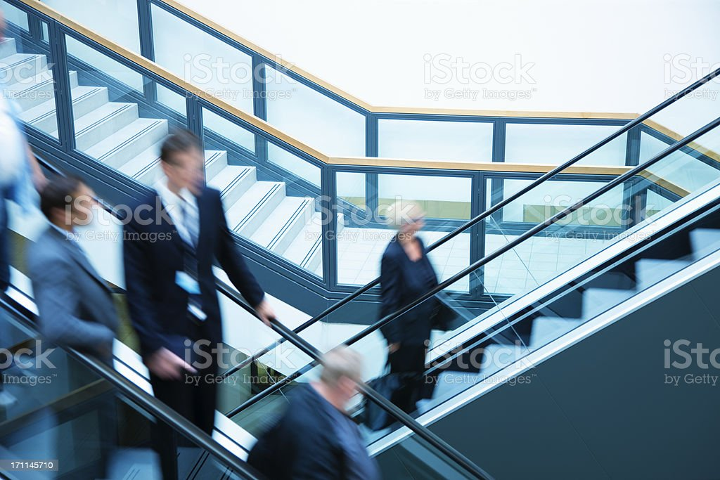 Business people on escalators, blurred motion stock photo