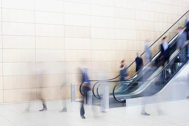 uomini d'affari su scale mobili - escalator foto e immagini stock