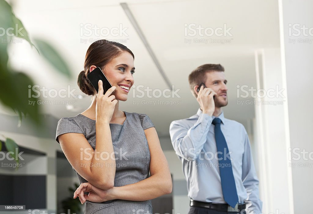 Business people on the phones Smiling businesswoman and businessman talking on the phone. Adult Stock Photo